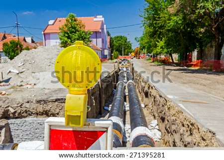 Construction site is protected by fence with flashing beacon lights for safety. - stock photo