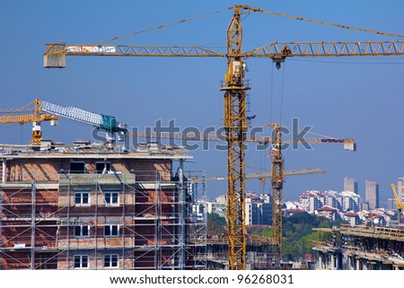 Construction site, lot of cranes and buildings - stock photo