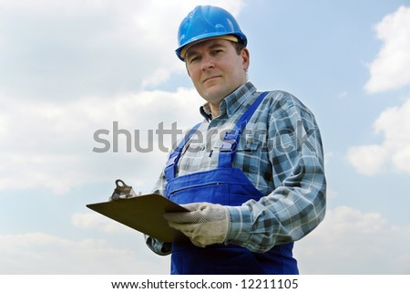 Construction site manager wearing blue helmet and overall with notepad over sky background - stock photo