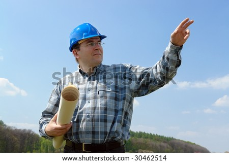 Construction site manager wearing blue helmet holding roll of building plans pointing ahead with his hand - stock photo