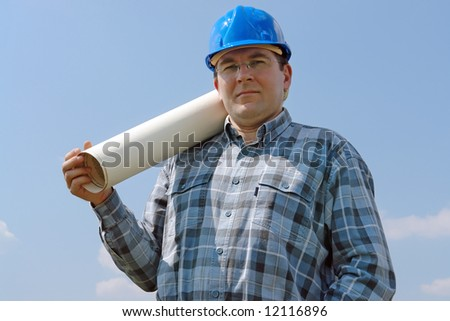 Construction site manager wearing blue helmet posing with roll of building plans over blue sky