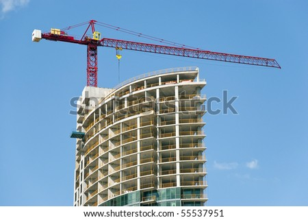 Construction site - modern semicircle shaped building and the red crane. - stock photo