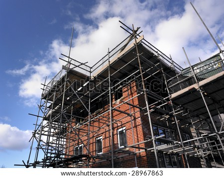Construction site scaffolding on the side of new building - stock photo