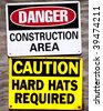 Construction site signage. Two fastened to same wood fence. Danger Construction Area and Caution Hard Hats Required - stock photo