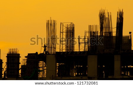 Construction site, silhouettes of workers against the light - stock photo