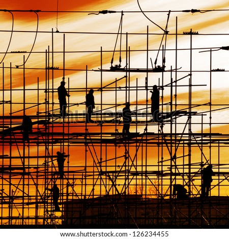 Construction site, silhouettes of workers on scaffolding against the light - stock photo