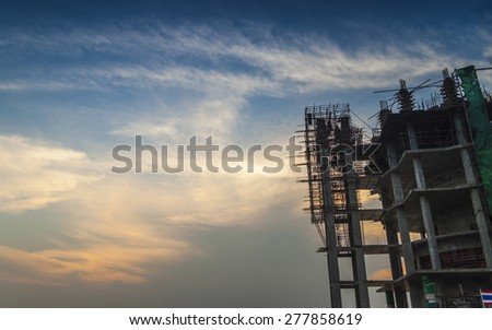 construction site silhouettes on the sunset background - stock photo