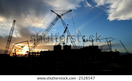 Construction Site Sillouhette with Multiple Cranes at Sunset - stock photo