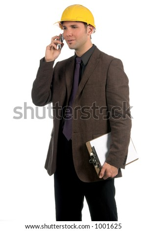 Construction site superintendent in a business suit and hard hat with a cell phone - stock photo