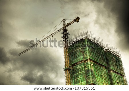 construction site under cloudy sky with green net and scaffold as protection. - stock photo