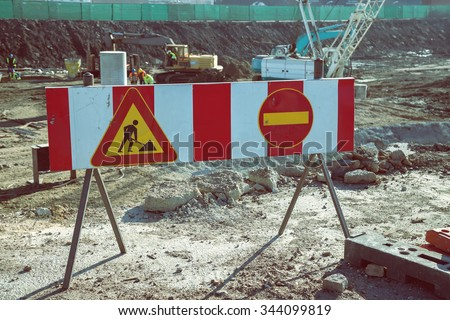 Construction site warning sign in front of construction site with machinery and workers. Construction site barrier in the new development area. Made with shallow dof and vintage style. - stock photo