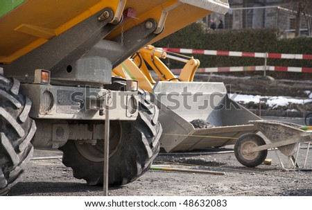 Construction site - wheelbarrow, tipper and loader - stock photo