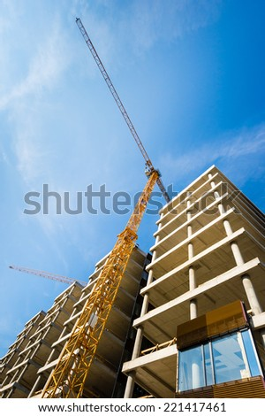 Construction site with building with yellow crane and blue sky - stock photo