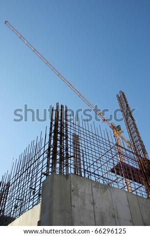 Construction site with concrete and steel and crane lifting equipment - stock photo