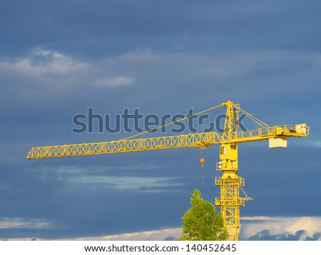 Construction site with crane and building and stormy cloud blue sky - stock photo
