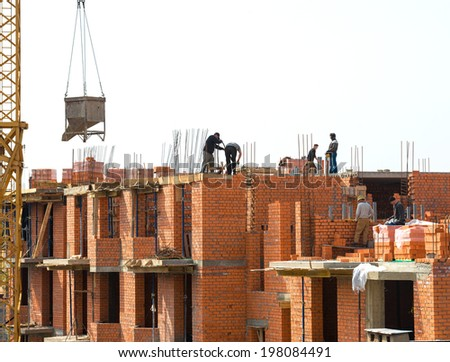 Construction site with crane and workers - stock photo