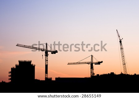 Construction site with cranes and city skyline at sunset