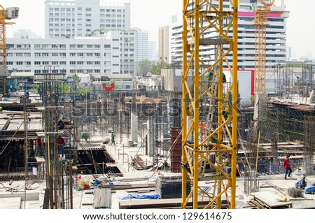 Construction site with  cranes and many workers - all logos are removed - stock photo