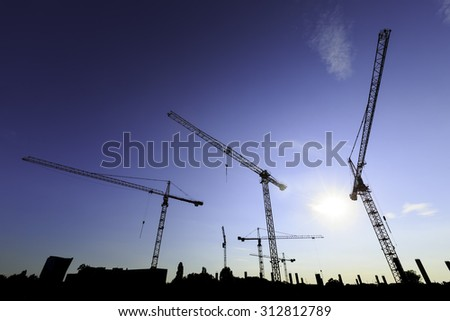 construction site with cranes at sunset