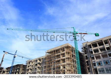 Construction site with cranes on blue sky background - stock photo