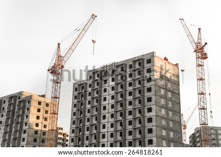 Construction site with cranes on sky background.