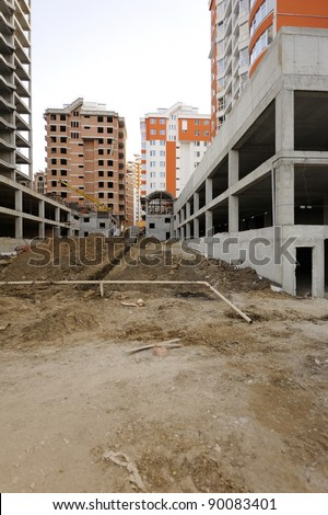 Construction site with great perspective showing finished houses in the background. Useful file for your construction site, brochure or advertising about your new apartment complex. - stock photo