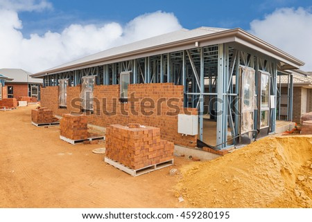 Construction site with homes from brick with metal framing against a blue sky.House construction site - stock photo