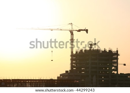 Construction Site With Huge Crane In An Exotic Evening Light - stock photo