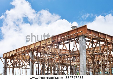 Construction site with scaffolding against blue clear sky - stock photo