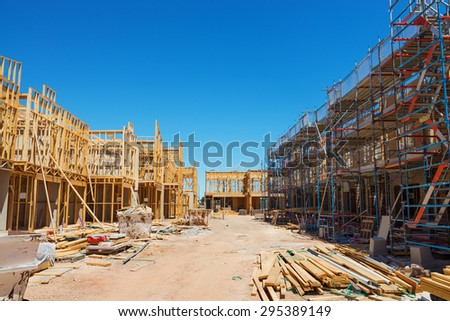 Construction site with the house in scaffolding against a blue sky - stock photo