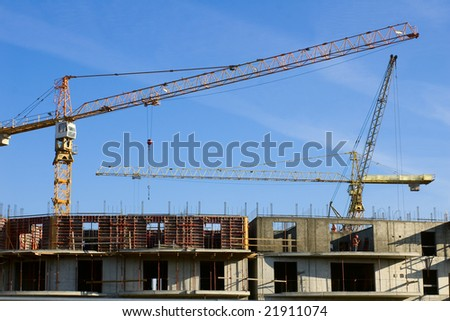 construction site with two building cranes against blue sky