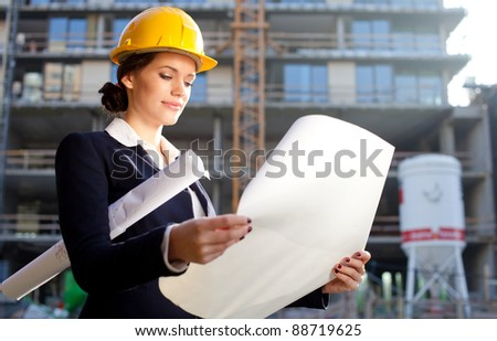 Construction specialist looking at blueprints at construction site - stock photo