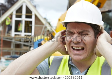 Construction Suffering From Noise Pollution On Building Site - stock photo