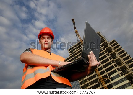 Construction supervisor in safety helmet and reflex vest with notebook in front of construction site.