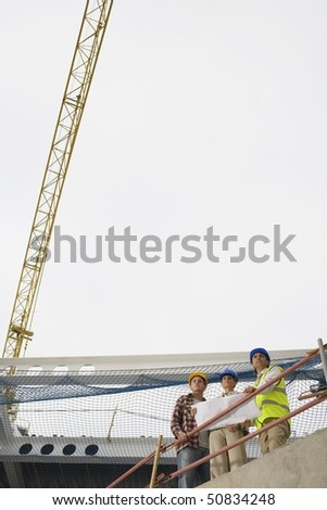 Construction team examining building plans on site - stock photo