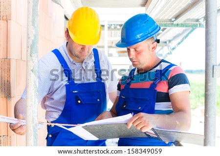 Construction Team with building plans on site - stock photo