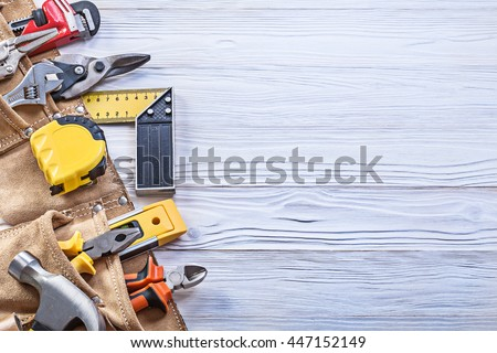 Construction tooling in leather toolbelt on wooden board copy space maintenance concept.