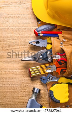 construction tools  in toolbelt hammer tapeline wrench nippers pliers cutter pencil screwdriver helmet on wooden board  - stock photo
