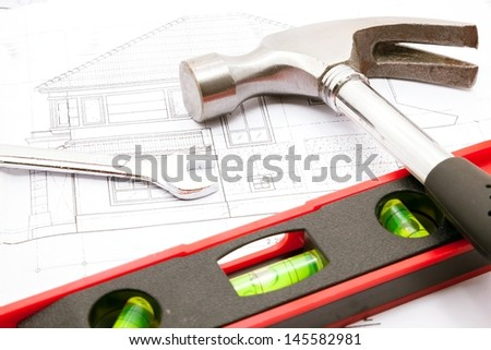 Construction tools over a construction drawing of a house blueprint - stock photo