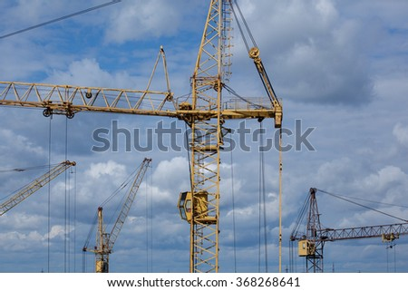 Construction tower cranes against a blue sky