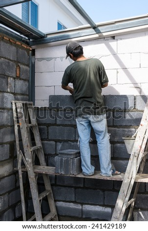 Construction wall of modern house with man worker. - stock photo