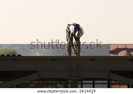 Construction welder on the roof of a building tacking down a steel roof. - stock photo