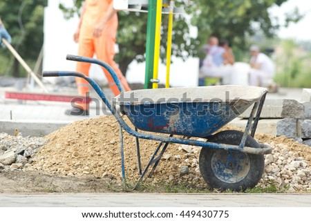 Construction wheelbarrow standing beside gravel and concrete curb stones at building site. Workers in background - stock photo