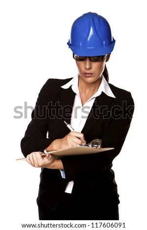 Construction woman. A female building inspector holding a clipboard and wearing a hardhat on a white background. - stock photo