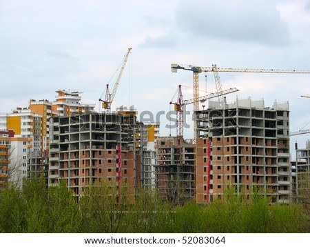Construction work site place concept with cranes and buildings over sky background - stock photo