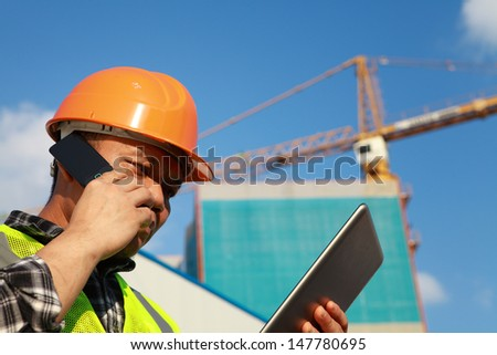 Construction worker activity with mobile phone and digital tablet - stock photo