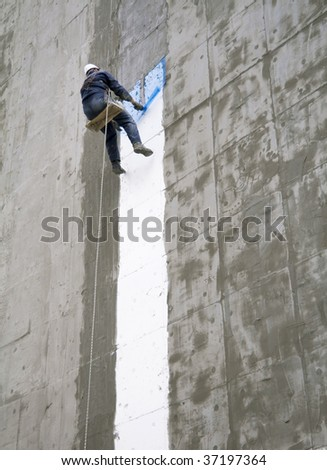Construction worker and grey cement wall white line - stock photo