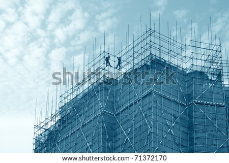 construction worker assembling scaffold on building site with sky background - stock photo
