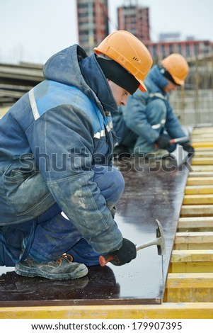 construction worker at construction site assembling falsework for concrete pouring