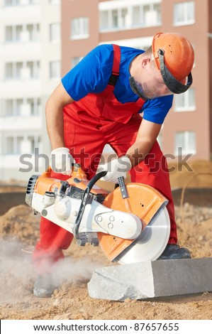 construction worker at curb stone cutting work by cut-off saw with diamond wheel - stock photo